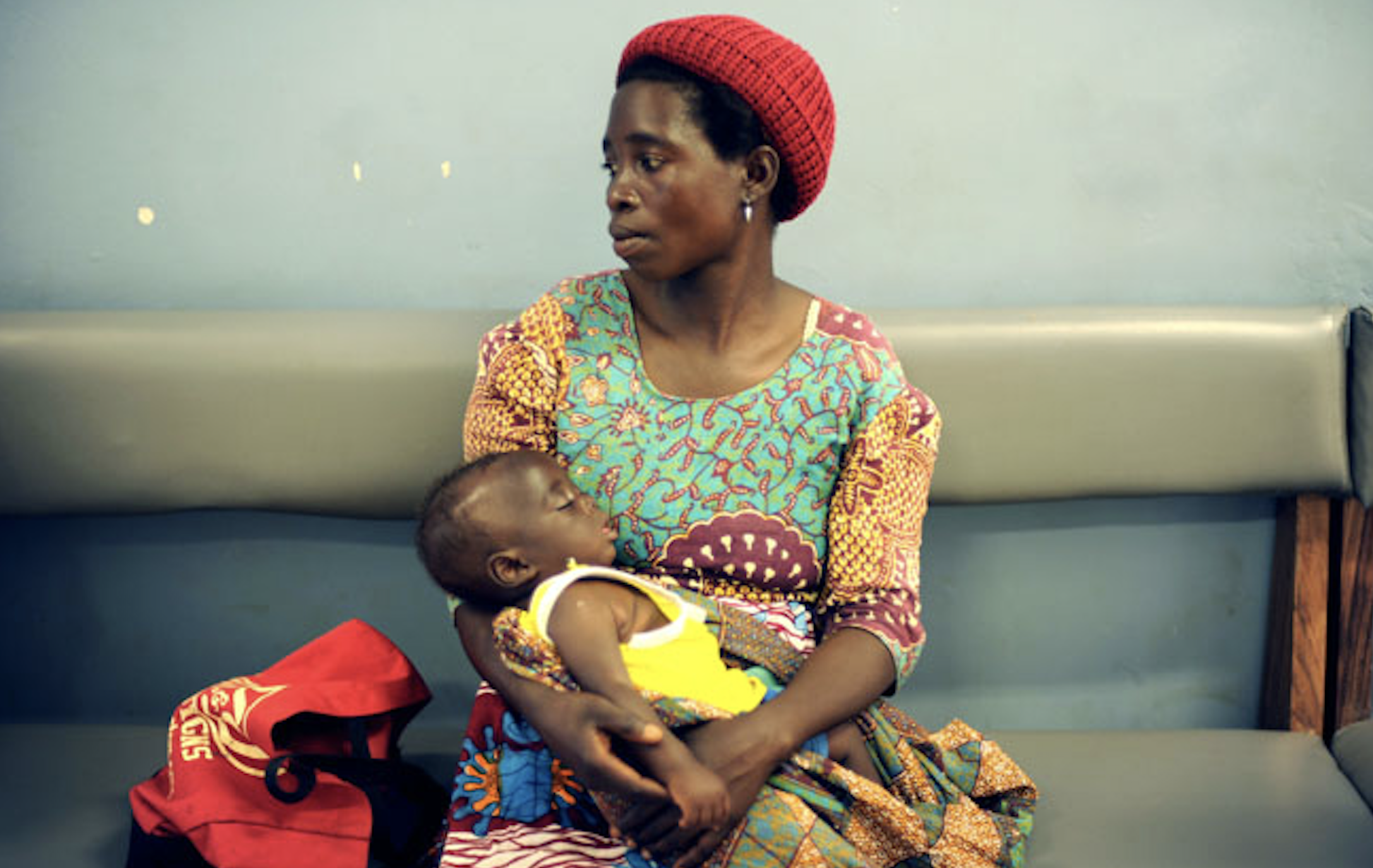 African woman holding a baby in her arms at a hospital